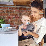 A beautiful mom is sitting at a white table in a rustic-looking kitchen with her 3 year old son on her lap. The boy is holding a soother with a tribal theme