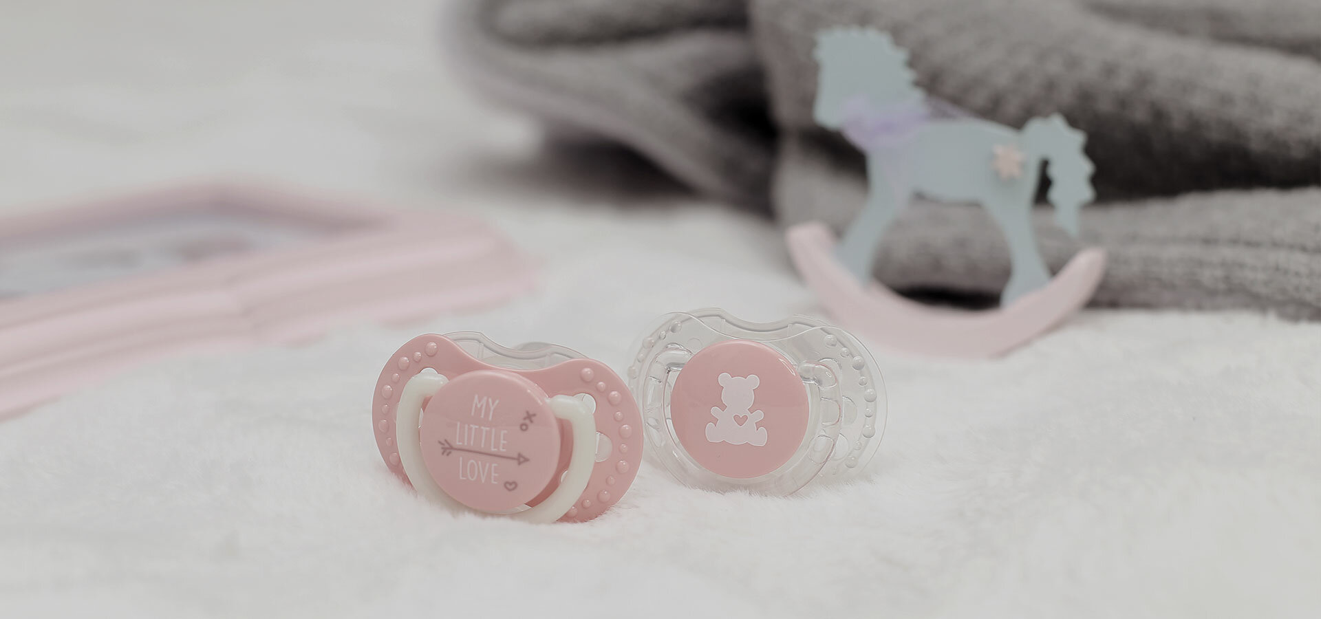Two pink LOVI soothers lying on a white blanket.