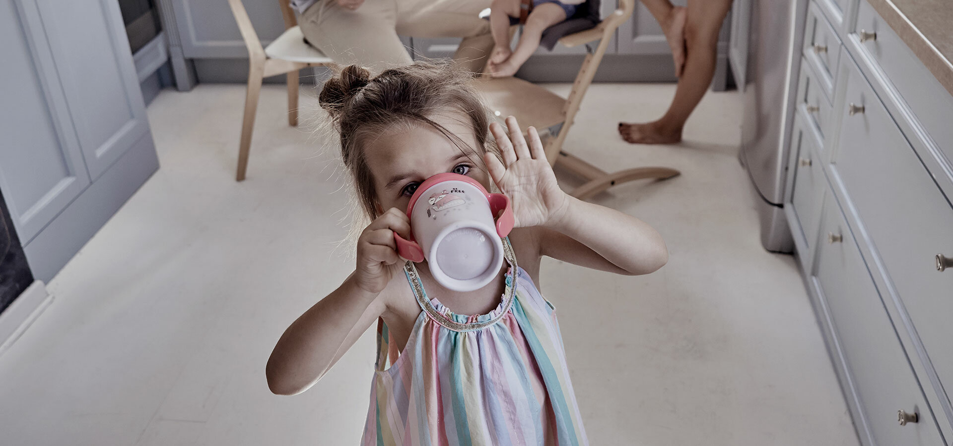 Girl about a 4 years old, drinking from a LOVI 360 Cup.