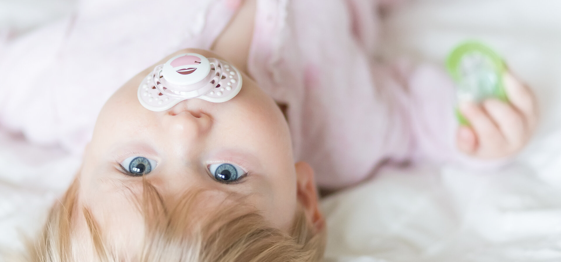 A baby girl is lying in bed with a lovi soother