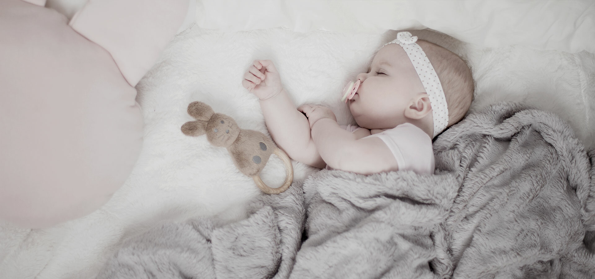 A baby girl is calmy sleeping on a white bed under a soft grey blanket.