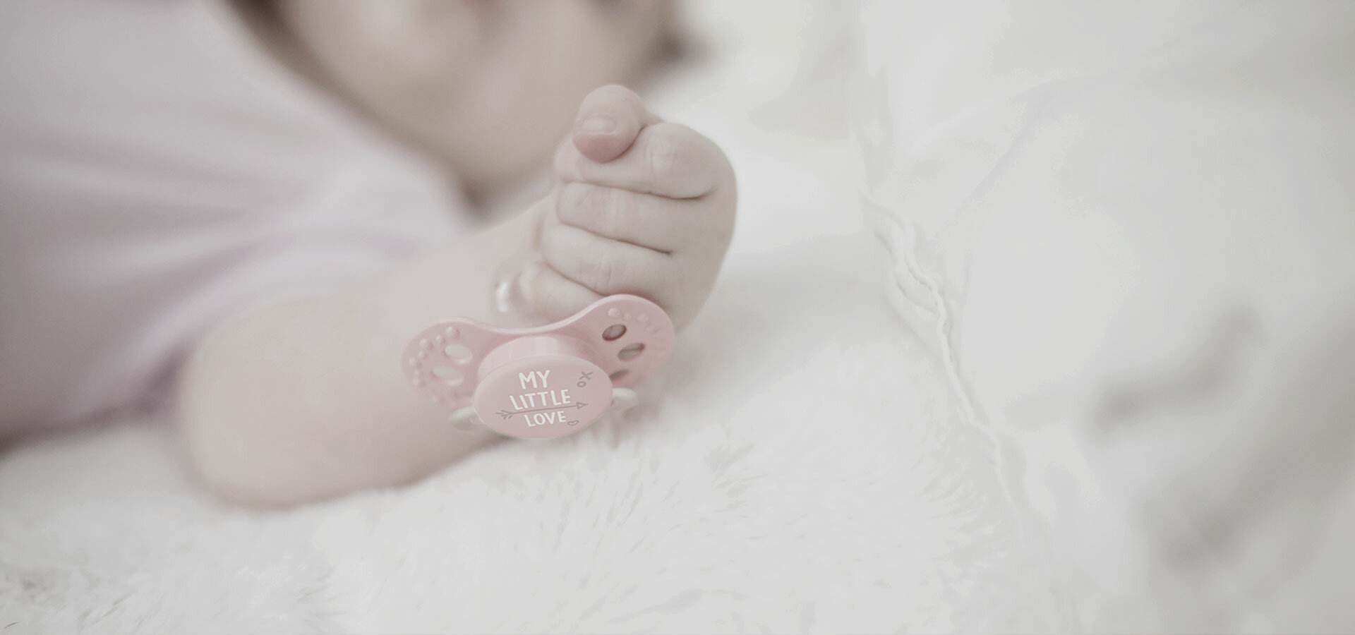Small babys hand holding a pink mini soother