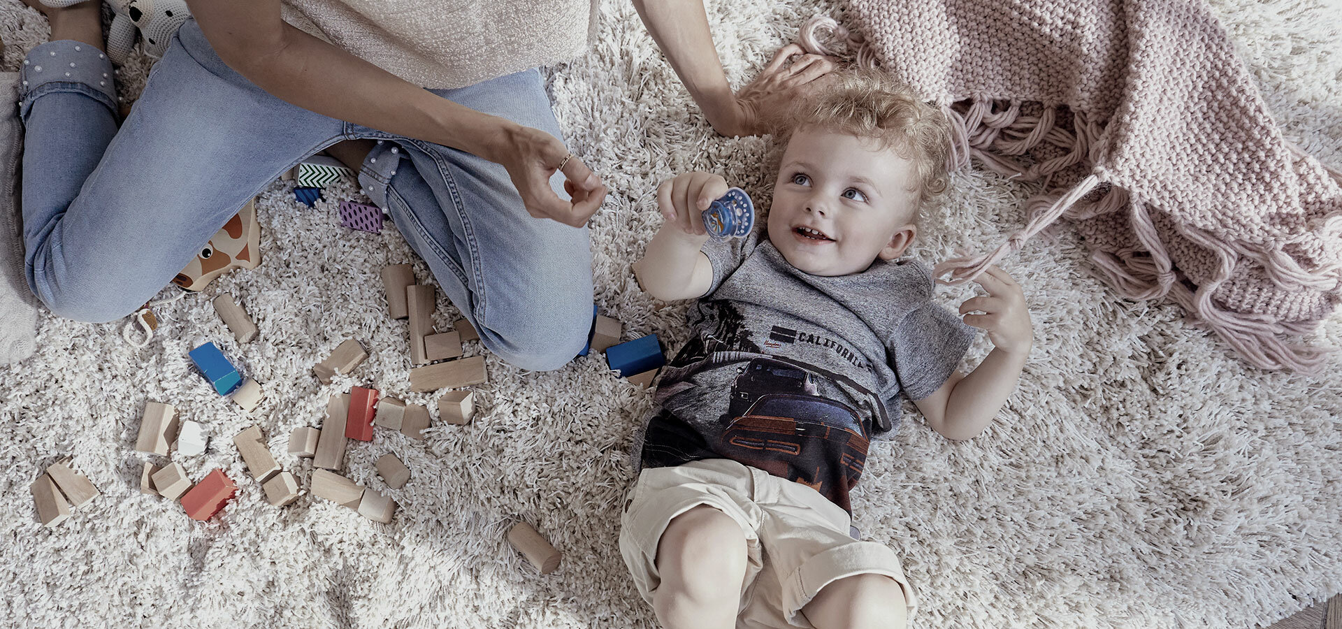 A small smiling boy is lying on a rug with a soother pacifier LOVI in his hand.
