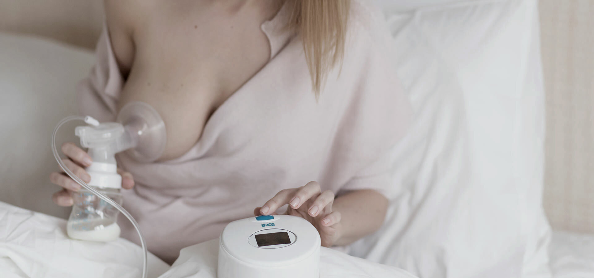 A woman using LOVI Prolactis electronic breast pump.